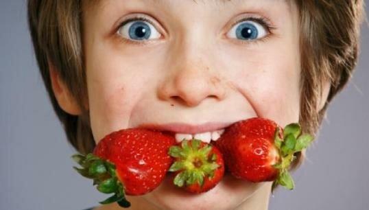 Мальчик с полным ртом клубники